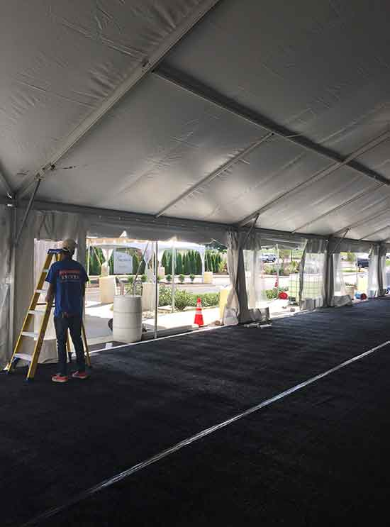 Setting up a tent rental for a ribbon cutting event